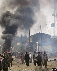 Groups of Kikuyu groups roam the streets of a neighborhood of Naivasha as fires burn