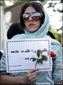 "Iranian woman at a protest against discrimination holding a banner reading: ""Cruelty to women equals cruelty to society and humanity'"" (June 2005)"