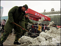 Chinese soldiers clear snow in Shanghai on 29 January 2008