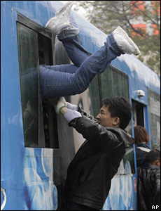 A man pushes a woman into a bus which will take them to the Guangzhou Railway Station, China (30/01/2008)