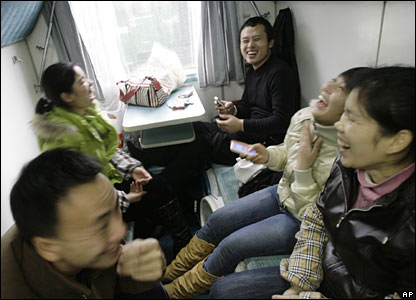 Passengers smile after getting on a train at Guangzhou Railway Station, China (30/01/2008)