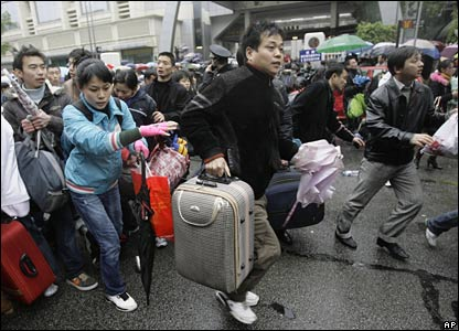 Passengers rush to a bus which will take them to Guangzhou train station, China (30/01/2008)