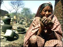 Muslim woman prays near her destroyed home after mobs torch Muslim homes in Ahmadabad