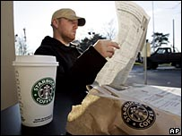 Man reads newspaper in Starbucks coffee shop