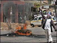 A man walks past burning a tire in downtown Eldoret (17 January)