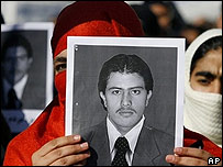 A member of the Solidarity Party of Afghanistan holds a picture of Pervez Kambakhsh