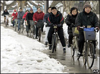 People cycle through snow-hit streets in Nanjing on 31 January 2008