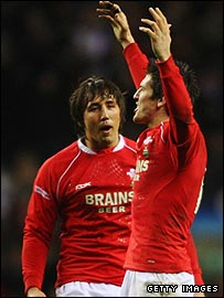 James Hook raises his arms in triumph as Gavin Henson looks on