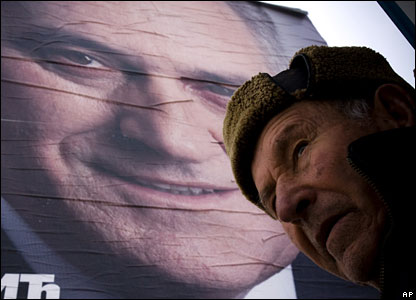 A man stands in front of an election poster of Tomislav Nikolic 3 February 2008