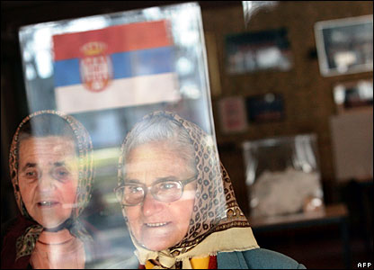 Elderly Serbian women are seen through a window of a polling station 3 February 2008