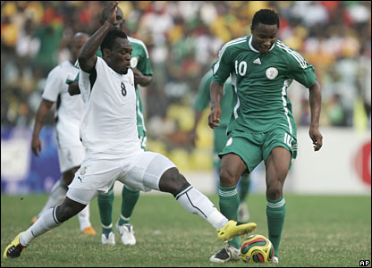 John Obi Mikel is challenged by Michael Essien