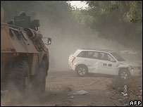 Car and French tank in aftermath of fighting in N'Djamena, Chad
