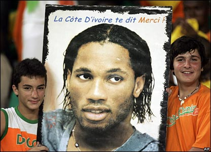 """Two children hold up a poster of Didier Drogba proclaiming """"La Cote d'ivoire te dit merci"""" (translation: """"The Ivory Coast thanks you"""")"""