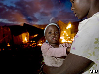 A resident of Kericho in western Kenya holds her baby in front of burning houses, 3 February 2008