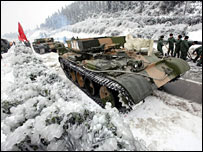 Armoured cars help clear snow and ice from a highway in Hunan province