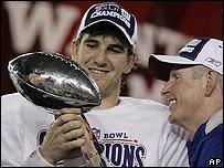 Eli Manning, de los Gigantes, y su entrenador, Tom Coughlin, miran el trofeo luego de la victoria