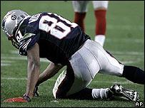Randy Moss, de Nueva Inglaterra, yace en el piso
