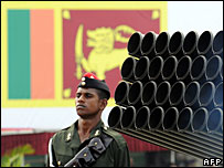 Army soldier stands beside a multi-barrel rocket launcher as he takes part in the military parade during independence day celebrations