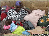 A woman sits with her child and belongings at a camp for internally displaced people in Thika, Kenya (01/02/2008)