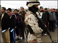 An Iraqi Army soldier secures the area as Iraqi men line up to submit their papers to join the police force in Doha (file photo)