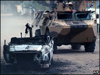 Un veh�culo militar franc�s pasa al lado de un veh�culo quemado