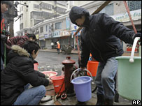 People collect water from a fire hydrant in Chenzhou, Hunan province (05/02/2008)