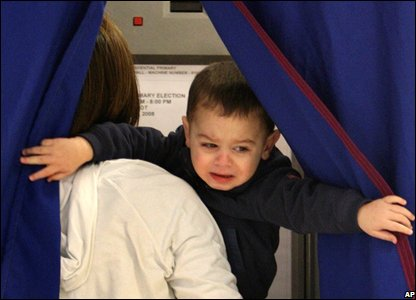 Ethan Yost attempts to get out of the voting booth while his mother Maria tries to cast her ballot