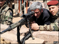 French Defence Minister Herve Morin looks through the barrel of a gun in Chad