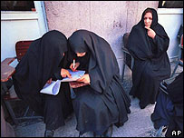 Iranian women study ballot sheets in 2004 parliament election
