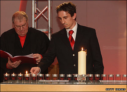Gary Neville lights a candle for each of the 23 people who died in Munich