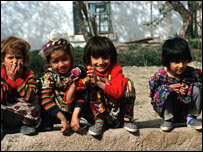 Tajik children sitting on a pavement