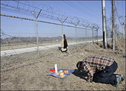 A man prays next to a barbed wire fence in Panmunjom, South Korea (07/02/2008)