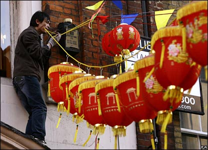 A man hangs traditional lanterns in London's Chinatown district (07/02/2008)