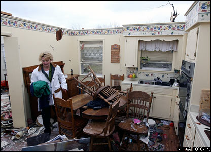 A woman searches through debris at her mother's house in Atkins, Arkansas