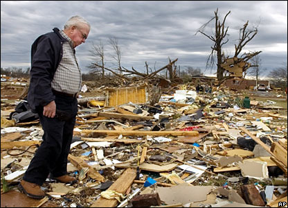 A man searches through the debris of his daughter's home in Lawrence County, Alabama