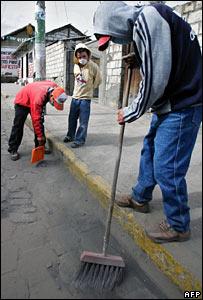 Residents sweep ashes from the street in Quero, Ecuador