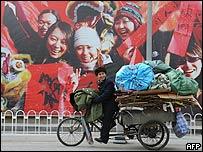 Ciclista chino recogedor de desperdicios reciclables junto a un anuncio en Pekín, enero 2008