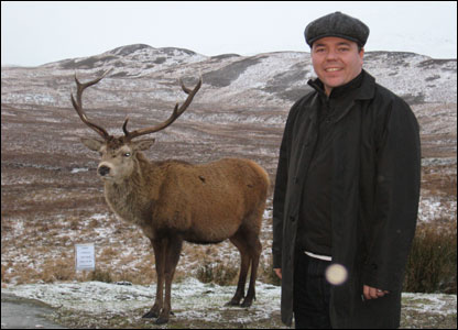 Man standing next to stag