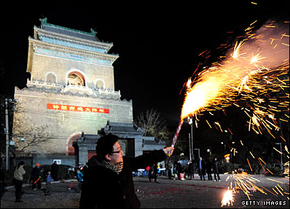 A man waves a firework to celebrate Lunar New Year in Beijing