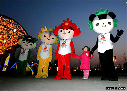 A girl poses for a photo with Chinese Olympic mascots