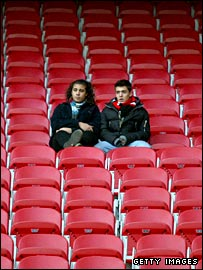 Two fans sit among a bank of empty seats