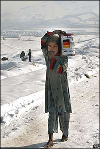 An Afghan girl takes home a can of food aid from Germany