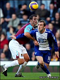 James McFadden (r) is bundled over by Lucas Neill