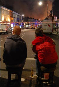 Two people sat watching the scene of the fire