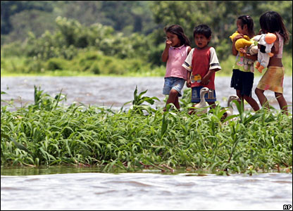 Children wade through a flooded area of Trinidad, 9 February 2008