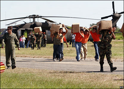 Soldiers carry boxes filled with supplies for victims of the floods in Trinidad, 9 February 2008