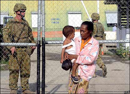 A woman and child walk past Australian peacekeeping troops at a checkpoint in Dili,  East Timor (11/02/2008)