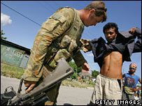 An Australian peacekeeper searches a man for weapons in Dili in June 2006