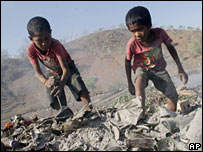 Two boys collect scraps of metal at a garbage dump in Tibar, East Timor