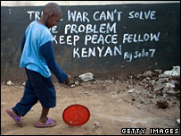 Boy playing in front of sign calling for peace